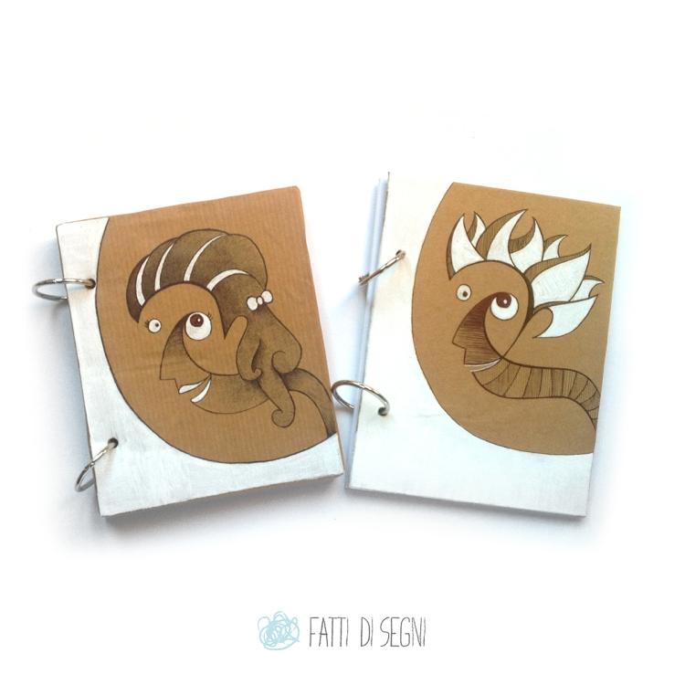 coppia di notes con copertina in cartone rivestito di carta da pacchi disegnata con pennarelli e penne a sfera.